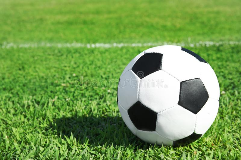 Soccer ball on fresh green football field grass. Space for text stock photography