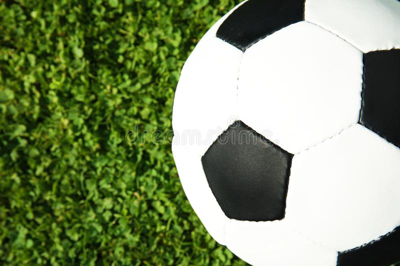Soccer ball on fresh green football field grass, top view. Space for text royalty free stock images