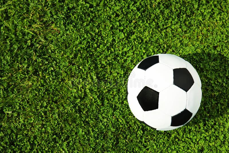 Soccer ball on fresh green football field grass, top view. Space for text stock photo