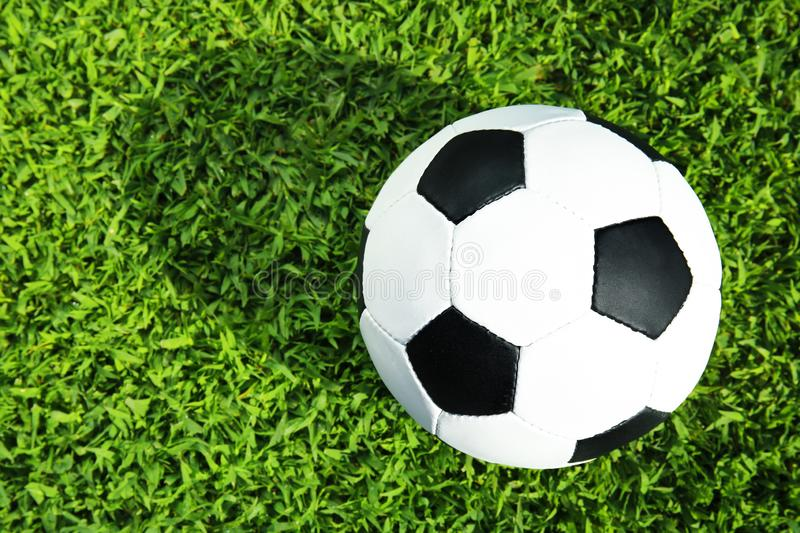 Soccer ball on fresh green football field grass, top view. royalty free stock photos