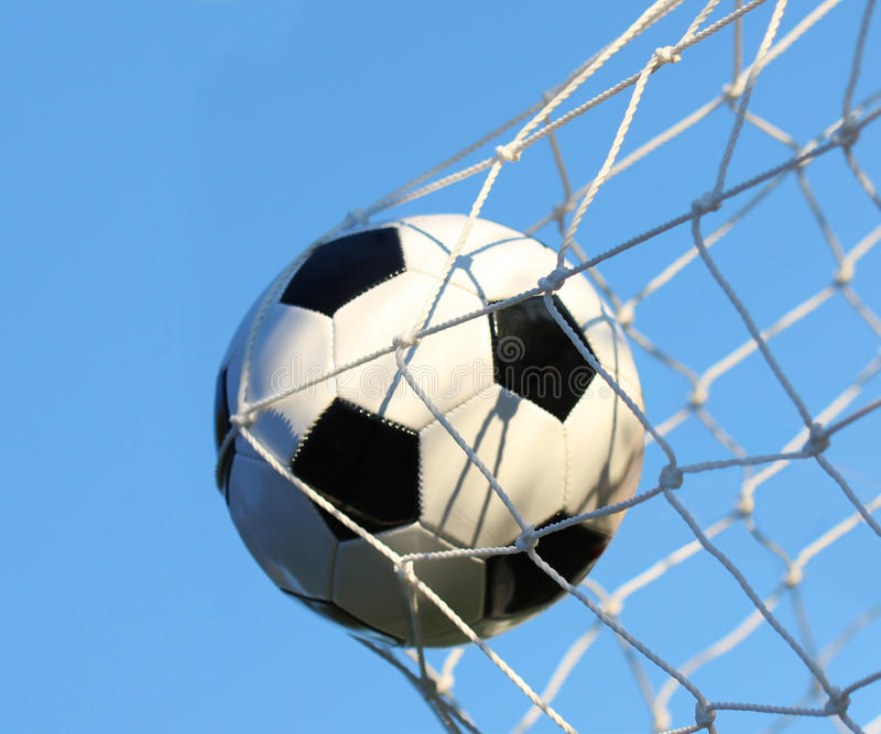 Soccer ball in goal net over blue sky. Football. Victory royalty free stock photography