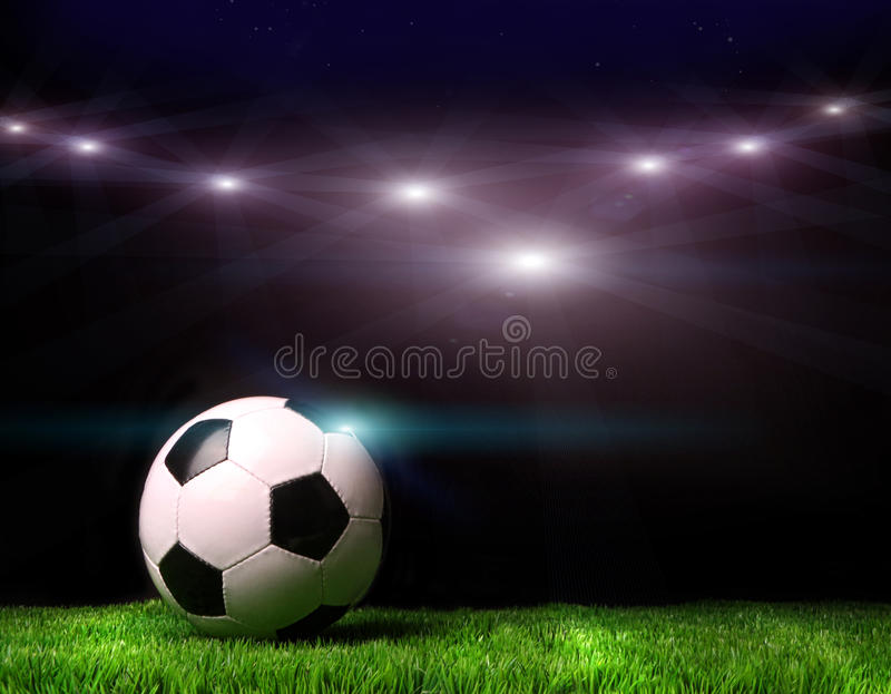 Soccer ball on grass against black stock image