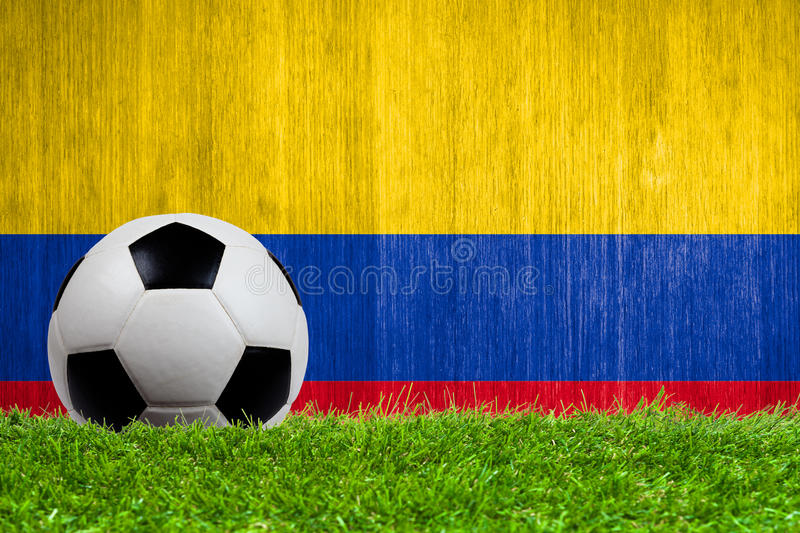Soccer ball on grass with Colombia flag background. Close up royalty free stock photography