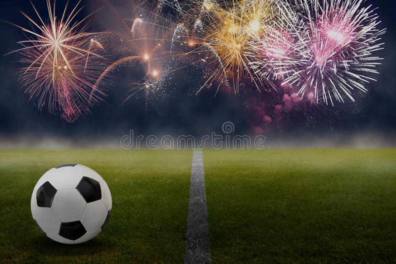 Soccer ball on the green against beautiful fireworks. Soccer ball on the green against beautiful colorful fireworks in the sky stock photography