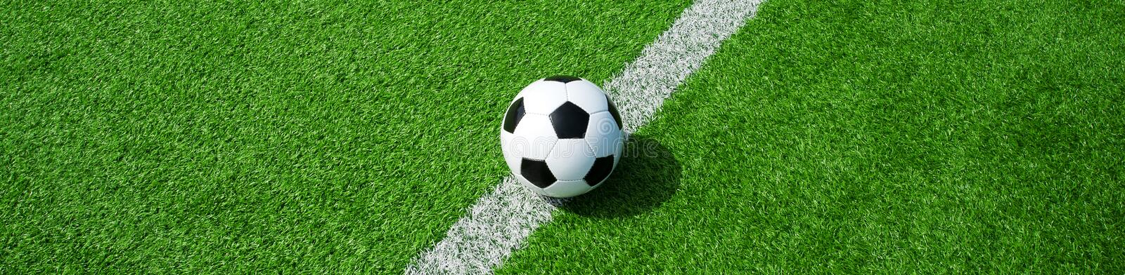 Soccer ball on green artificial grass, landscape format, for a banner. Soccer ball black and white on green artificial turf, space for text, good for banner royalty free stock photography