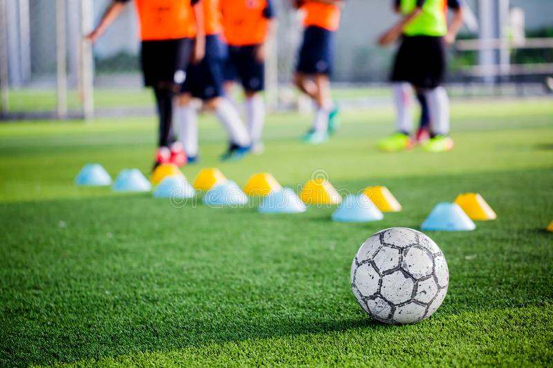 Soccer ball on green artificial turf with blurry of maker cones. And player training. Soccer academy royalty free stock images
