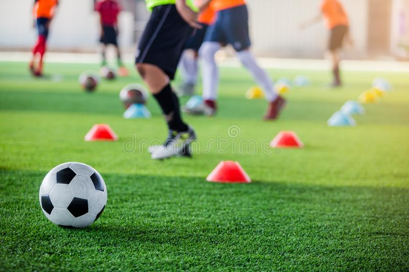 Soccer ball on green artificial turf with blurry of maker cones and player training. Soccer academy royalty free stock photo