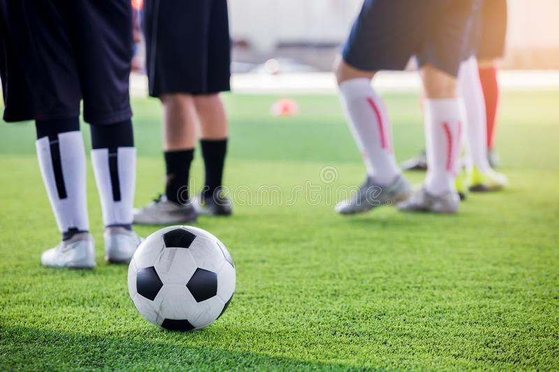 Soccer ball on green artificial turf with blurry soccer players. Standing before training and start game stock photos