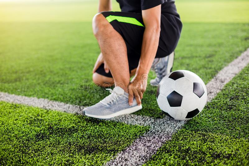 Soccer ball on green artificial turf with footballer is sitting and catch the ankle stock image