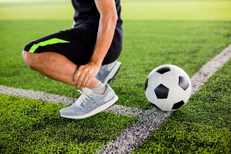 Soccer ball on green artificial turf with footballer is sitting and catch the ankle royalty free stock photography