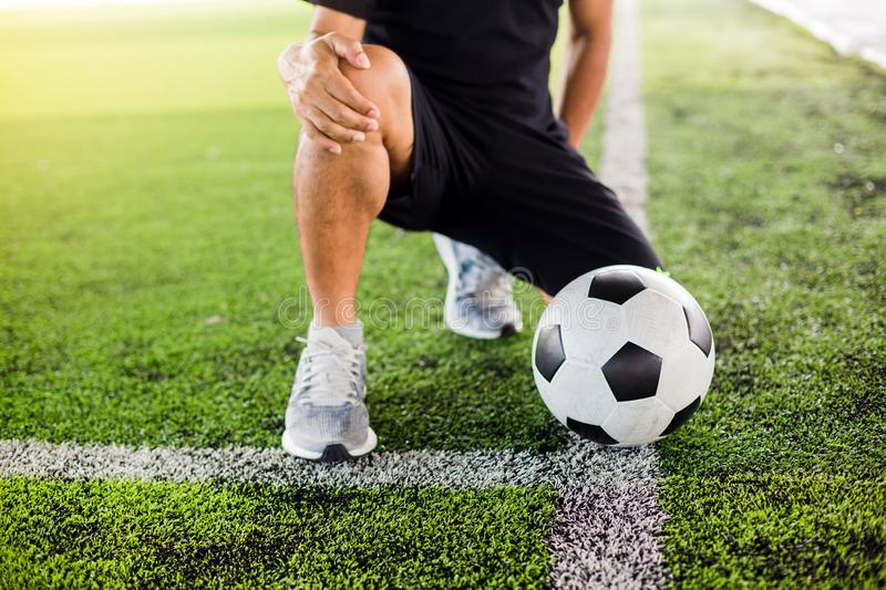 Soccer ball on green artificial turf with footballer is sitting and catch the knee royalty free stock photography