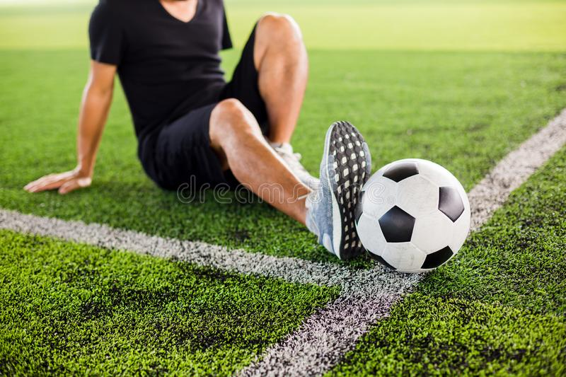 Soccer ball on green artificial turf with the player is stretch the muscles royalty free stock photos