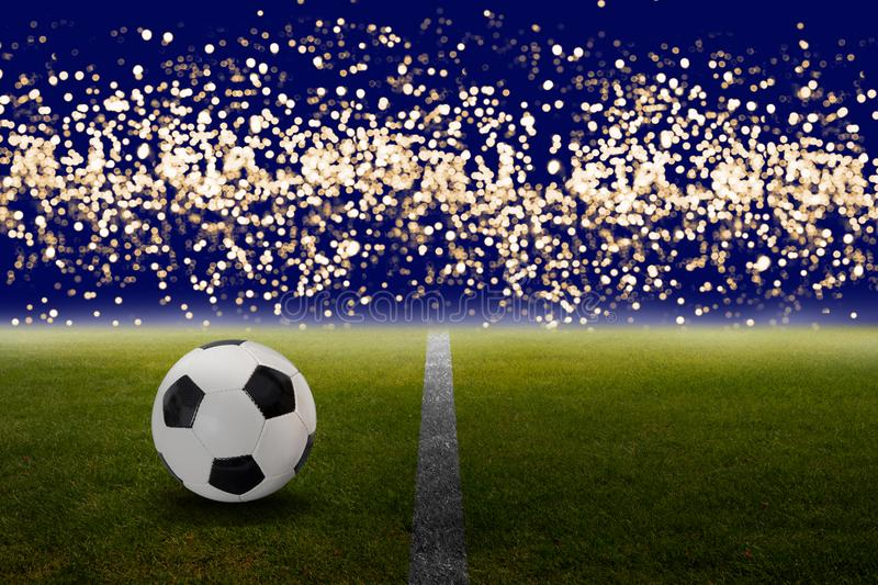 Soccer ball on the green with bokeh lights. Classic soccer ball or football on green grass field with blurred lights royalty free stock photo