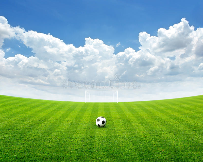 Soccer ball on the green field, Blue sky with cloud in summer. Day, soft focus royalty free stock photos
