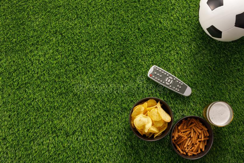 Soccer ball on a green field and ottoman for a fan with snacks and a TV remote control. flat lay.Copy space. Soccer ball on a green field and ottoman for a fan stock photography
