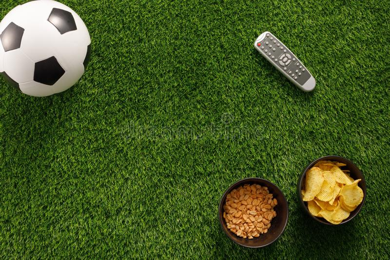 Soccer ball on a green field and ottoman for a fan with snacks and a TV remote control. flat lay.Copy space. Soccer ball on a green field and ottoman for a fan royalty free stock photography