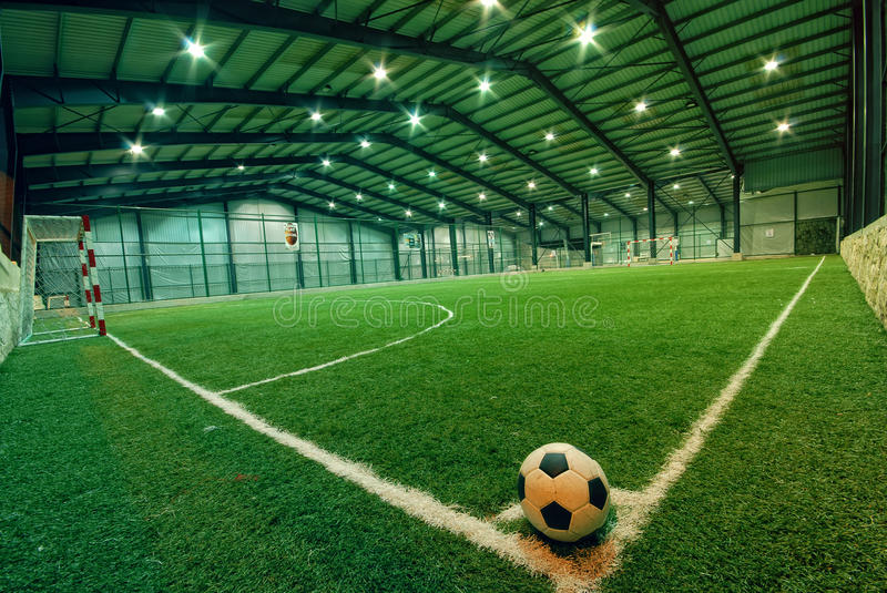 Soccer ball on green grass in an indoor playground stock photo