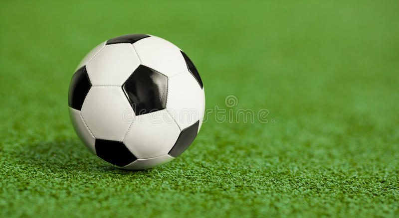 Soccer ball on green grass playground. Bokeh royalty free stock photography