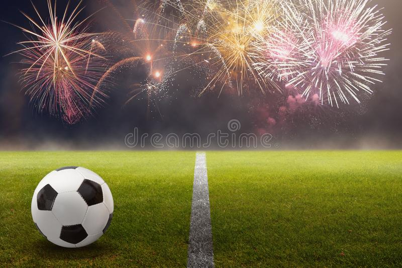 Soccer ball on the green against beautiful fireworks. Soccer ball on the green int he stadium against beautiful fireworks in the dark sky stock photo