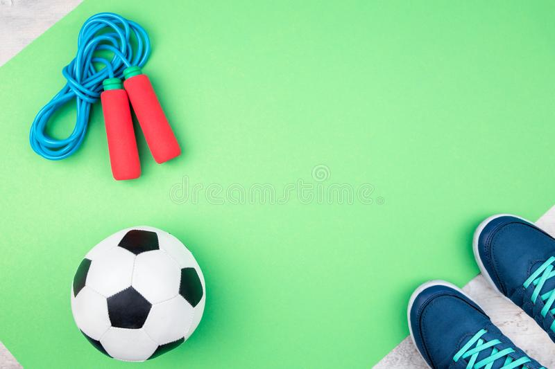 Soccer ball and jumping rope on green mat. Kids soccer ball for football with jumping rope and soccer shoes on a light green mat flat lay style royalty free stock images