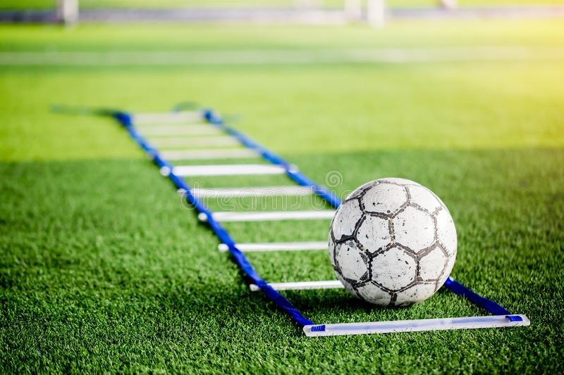 Soccer ball between ladder drills on green artificial turf for s. Occer training. Ladder drills exercises and soccer ball for football or soccer team stock image