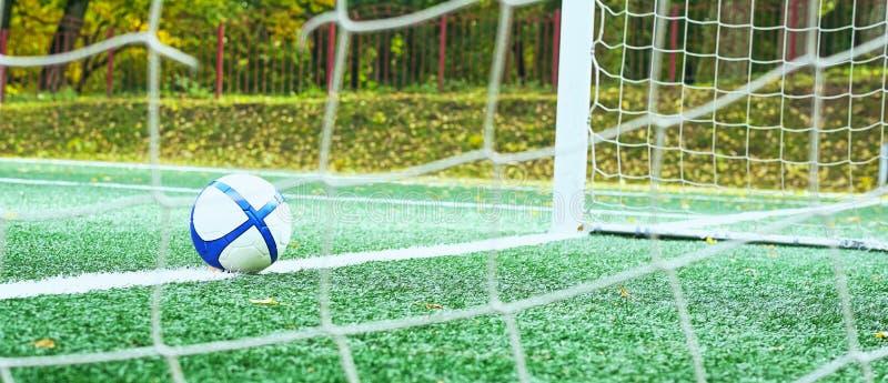 A soccer ball lies near white goal line markings on a green football field. Sport background. White soccer ball with blue stripes lies near white goal line royalty free stock photos