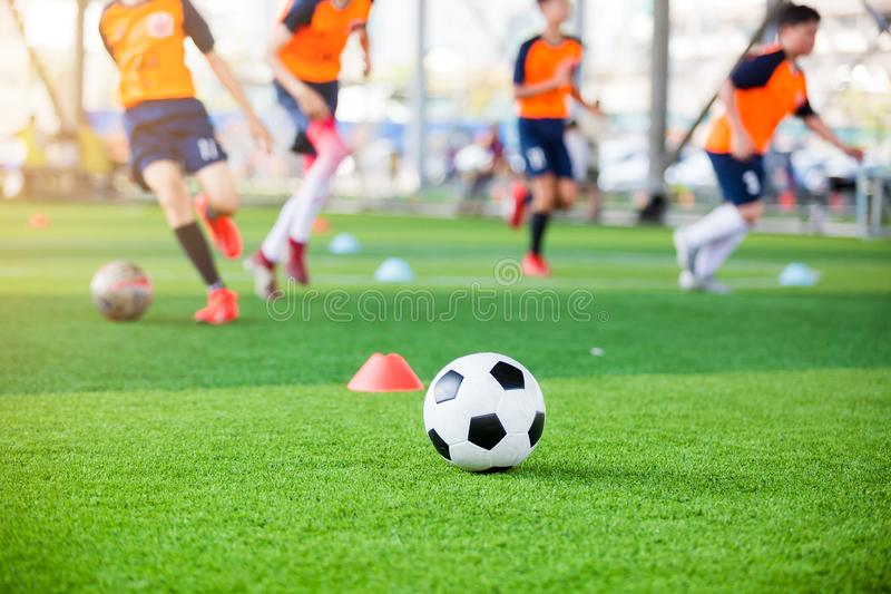 Soccer ball and marker cones on green artificial turf with blurry soccer team training. Blurry kid soccer player jogging between marker cones and control ball royalty free stock photography