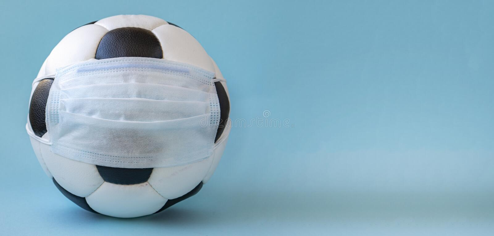 Soccer ball in a medical mask on a blue background. Corona protection against viruses bacteria stop. Cancellation of sporting events.Copy space royalty free stock photos