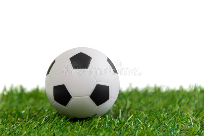 Soccer ball model on artificial green grass over white background stock photography