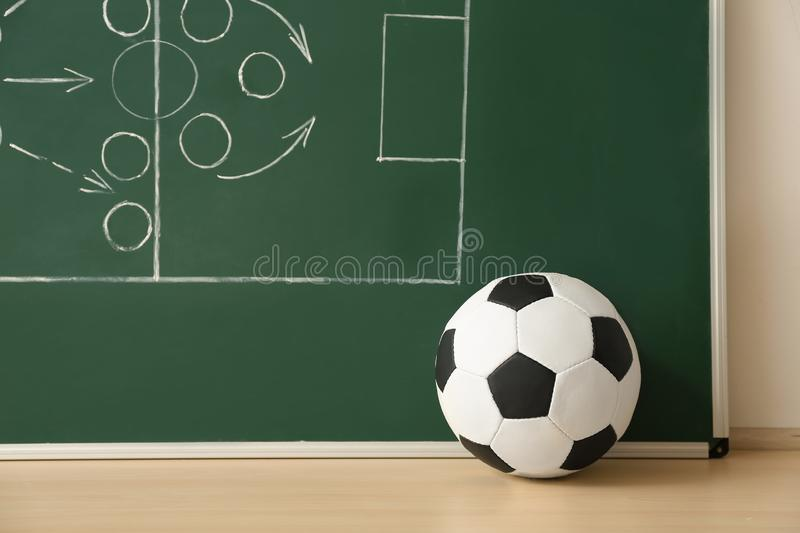 Soccer ball near chalkboard with football game scheme stock image