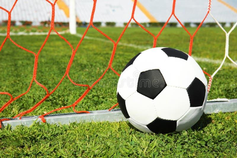 Soccer ball near net on green football grass. Soccer ball near net on green football field grass stock photos