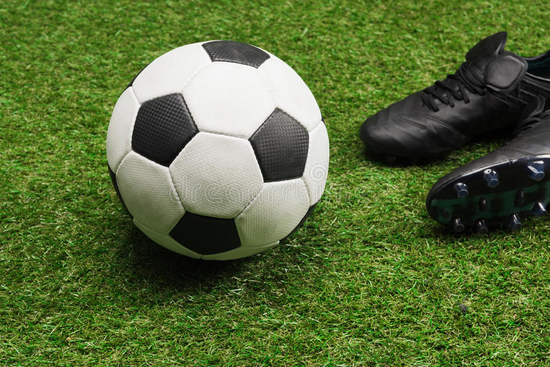 Soccer ball with pair of black sports shoes on grass stock image