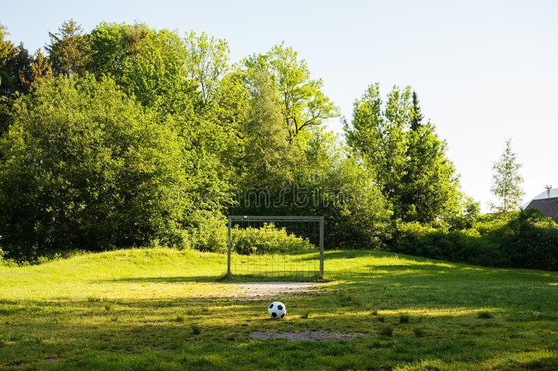 Soccer ball on penalty spot in natural football ground. For the youth, football for kids, friends meeting on weekend fun royalty free stock photo