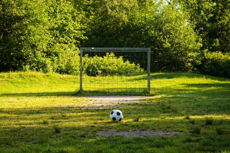 Soccer ball on penalty spot in natural football ground. For the youth, football for kids, friends meeting on weekend fun royalty free stock photography