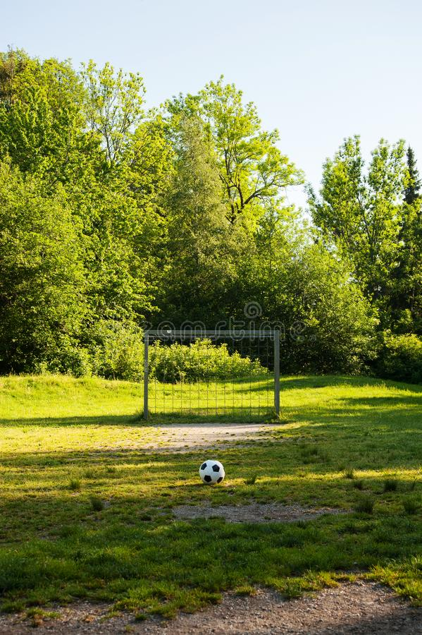 Soccer ball on penalty spot in natural football ground. For the youth, football for kids, friends meeting on weekend fun stock photography
