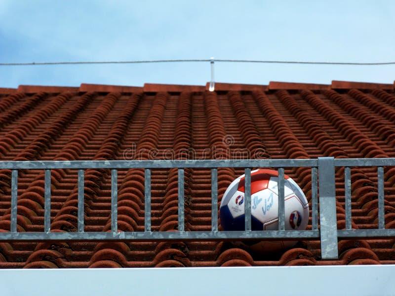 Soccer ball stuck on roof stock photo