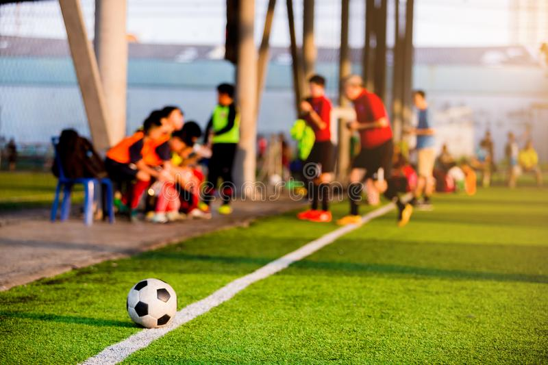Soccer ball at touchlines on artificial turf with blurry of soccer players. And coach are coaching in game royalty free stock image