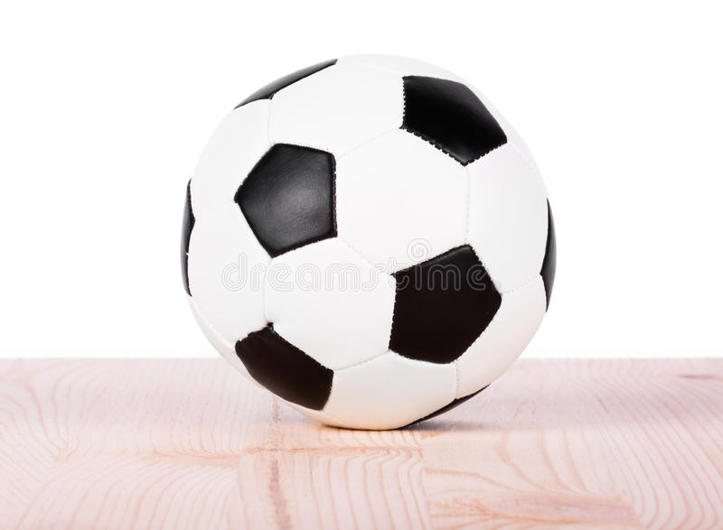 Soccer ball on wood shelf. On white background royalty free stock photography