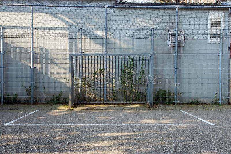 Soccer cage in the city, iron gate protection grid with soccer court behind it, empty. Soccer goal stock image