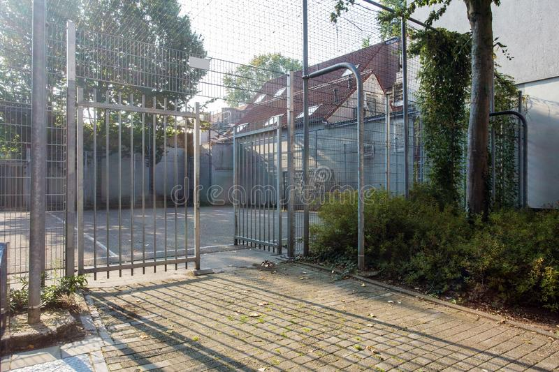 Soccer cage in the city, iron gate protection grid with soccer court behind it, empty. Soccer goal stock photo