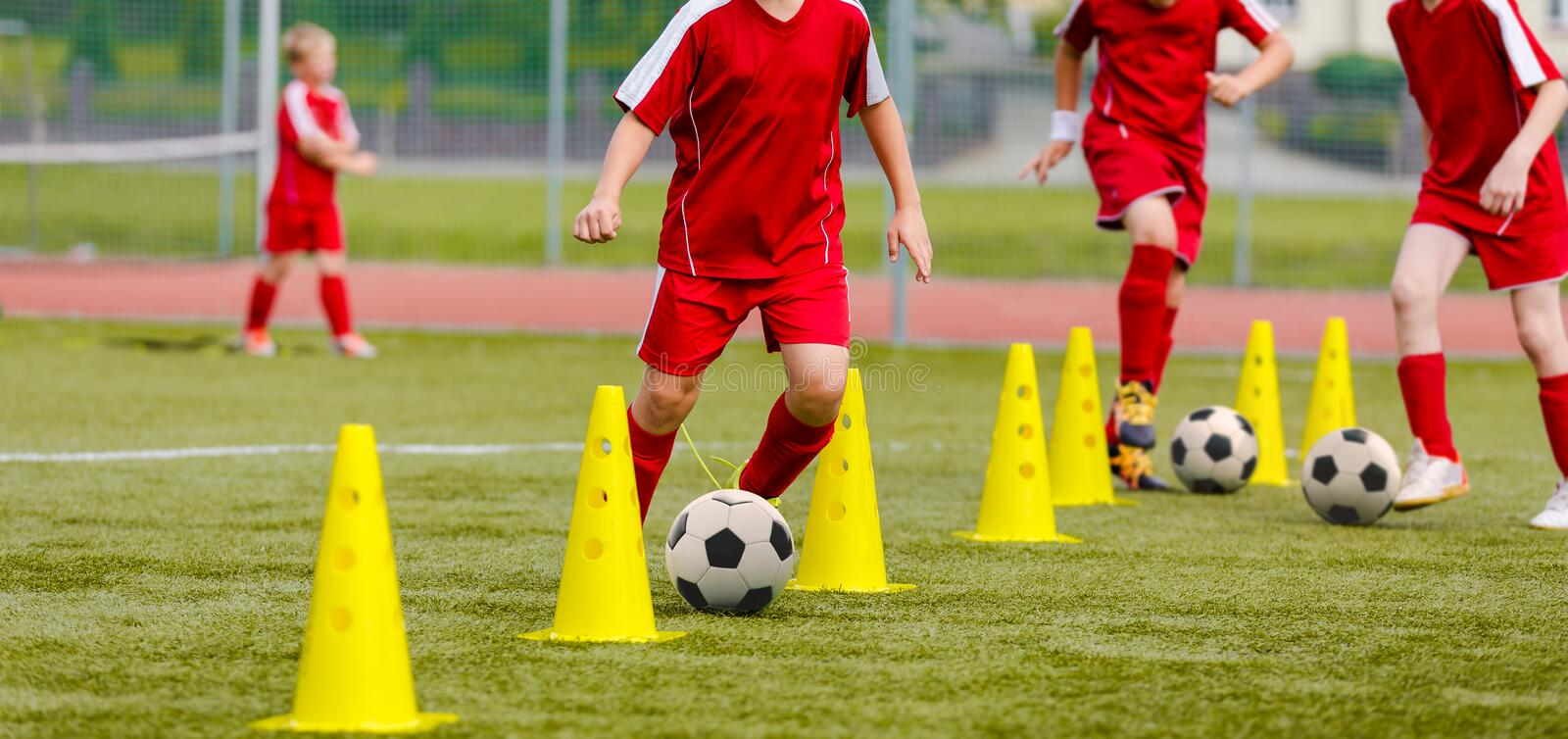 Soccer camp for kids. Boys practice dribbling in a field. Players develop good soccer dribbling skills. Children training with balls and cones. Soccer slalom royalty free stock photos