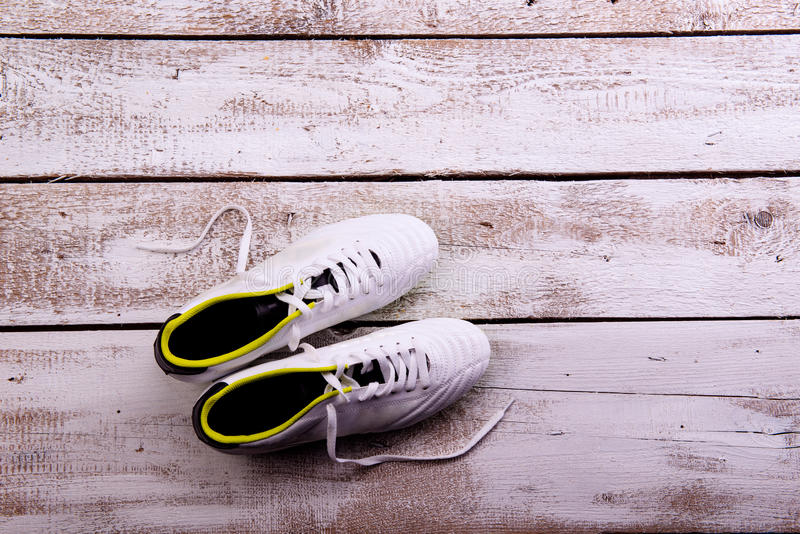 Soccer cleats against wooden background. Studio shot. Copy space. Soccer cleats against wooden floor, studio shot on white background. Copy space stock photo