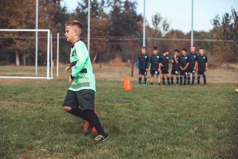 Young Footballer in a soccer jersey running between cones and ring ladder marker stock photos