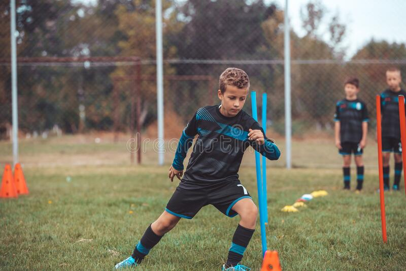 Young football player training on pitch royalty free stock photo