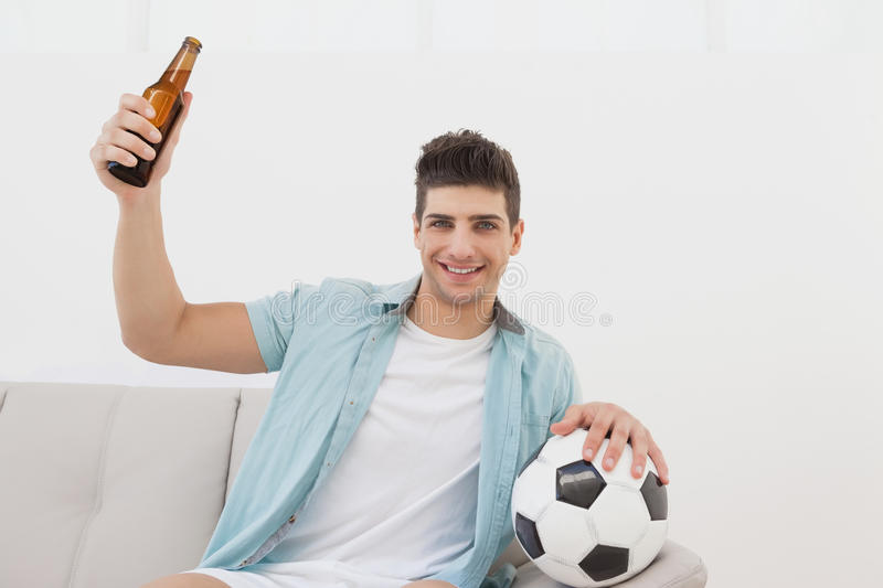 Soccer fan cheering while watching tv. Portrait of a happy soccer fan cheering while watching tv royalty free stock photography