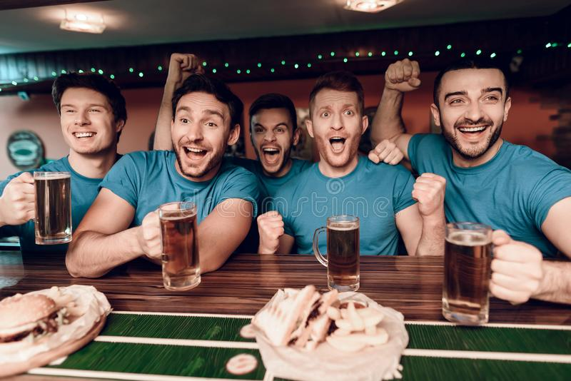 Soccer fans watching the game drinking beer and eating at sports bar. They are supporting blue team stock photography
