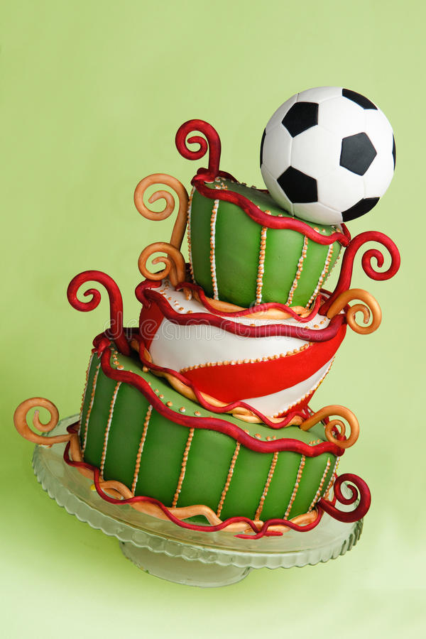 Soccer fantasy cake. Crooked curly cake in green, white, gold and red in soccer theme, with a football on top. Handmade cake with rolled fondant and sugar paste