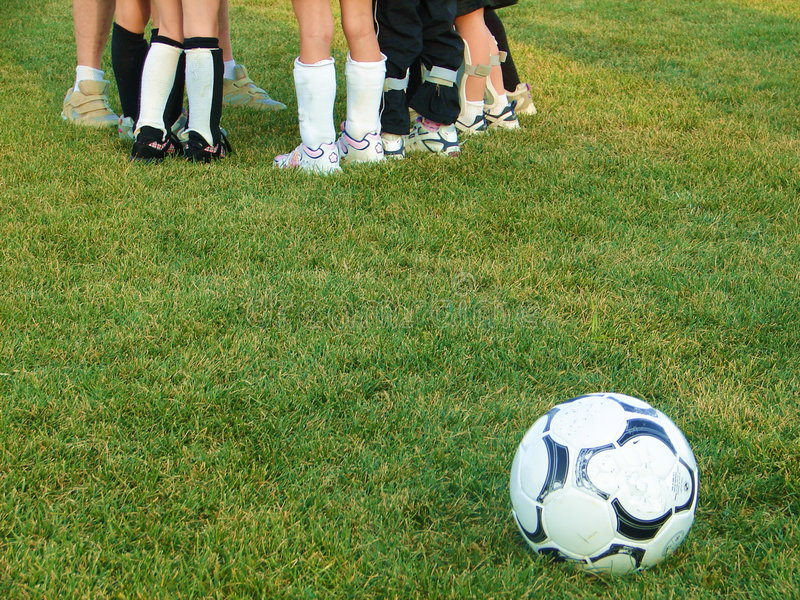 Soccer Feet. Ground view of soccer ball and players feet in background royalty free stock images
