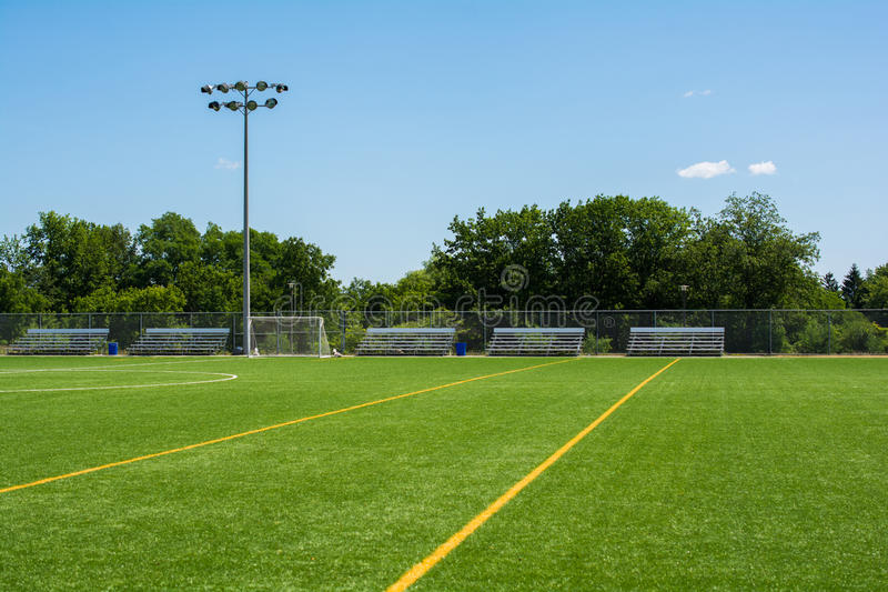 Soccer field with bleachers and light stand on a sunny day stock photos