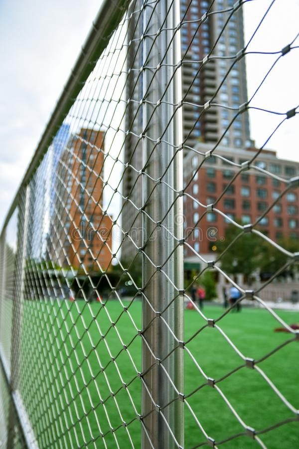 Soccer field concept out of focus in the city of NYC., Manhattan, between skyscrapers. Fence in the foreground focused. USA royalty free stock photography
